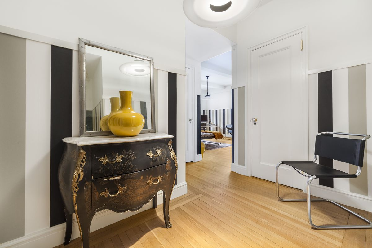 A foyer with an antique drawer, a mirror, and a yellow vase.
