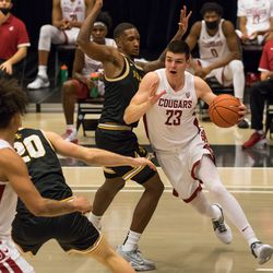 PULLMAN, WA - DECEMBER 9: Washington State forward Andrej Jakimovski (23) pushes past an Idaho defender during the second half of the Battle of the Palouse rivalry between the Idaho Vandals and the Washington State Cougars on December 9, 2020, at Beasley Coliseum in Pullman, WA.