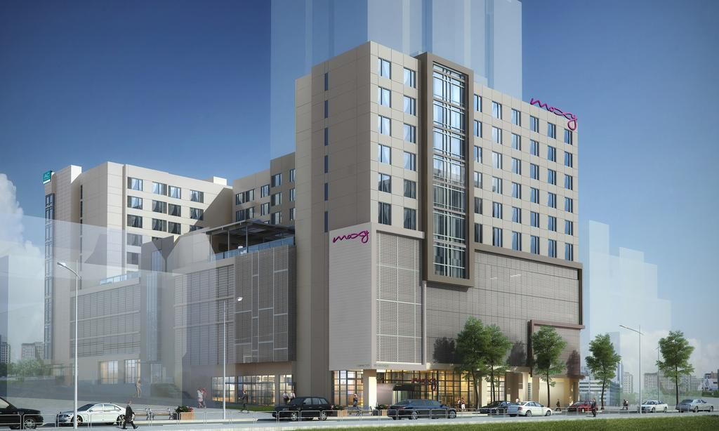 A six-story Moxy Hotel above a screened parking deck.
