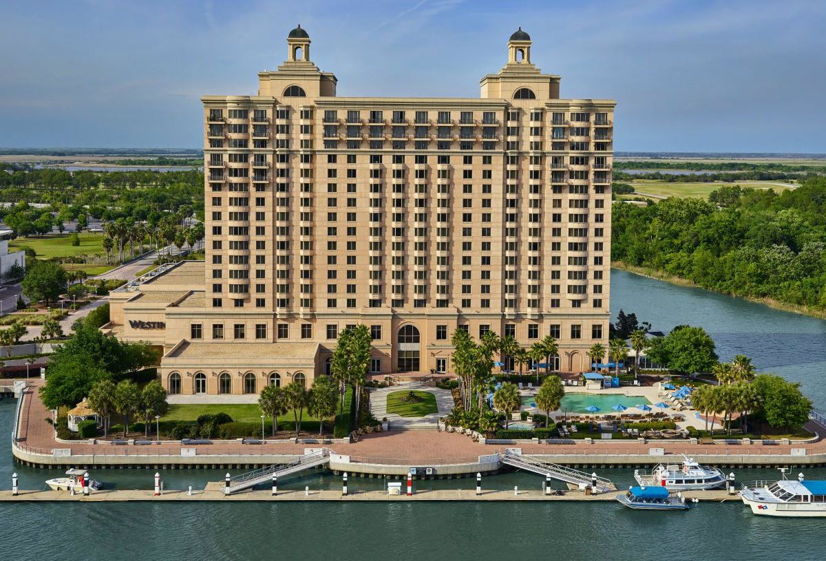 An aerial view of a large resort building surrounded by a body of water with a boat marina.