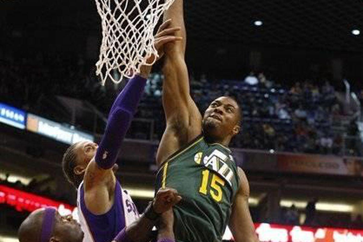Utah Jazz forward Derrick Favors (15) draws the foul on Phoenix Suns forward Michael Beasley (0) in the second quarter during an NBA basketball game on Friday, Dec. 14, 2012, in Phoenix. (Rick Scuteri/AP Photos)