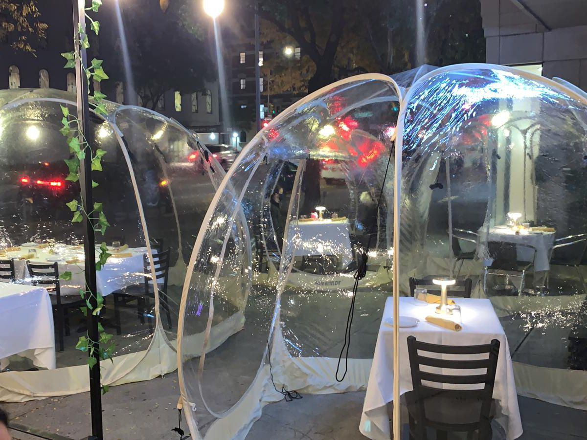 Plastic bubbles with dining tables and chairs setup inside