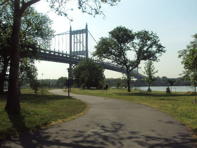 A park path. There is green grass on both sides of the path. In the distance is a large bridge.