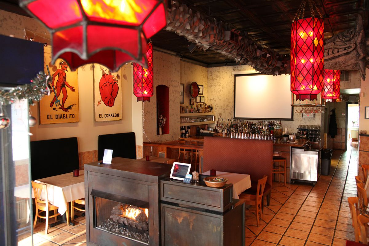 A cozy dining space with a fireplace, bar, and oversize Loteria cards on the wall.