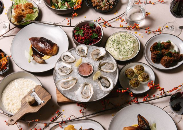 A row of oysters over ice are the center piece of a spread of dishes