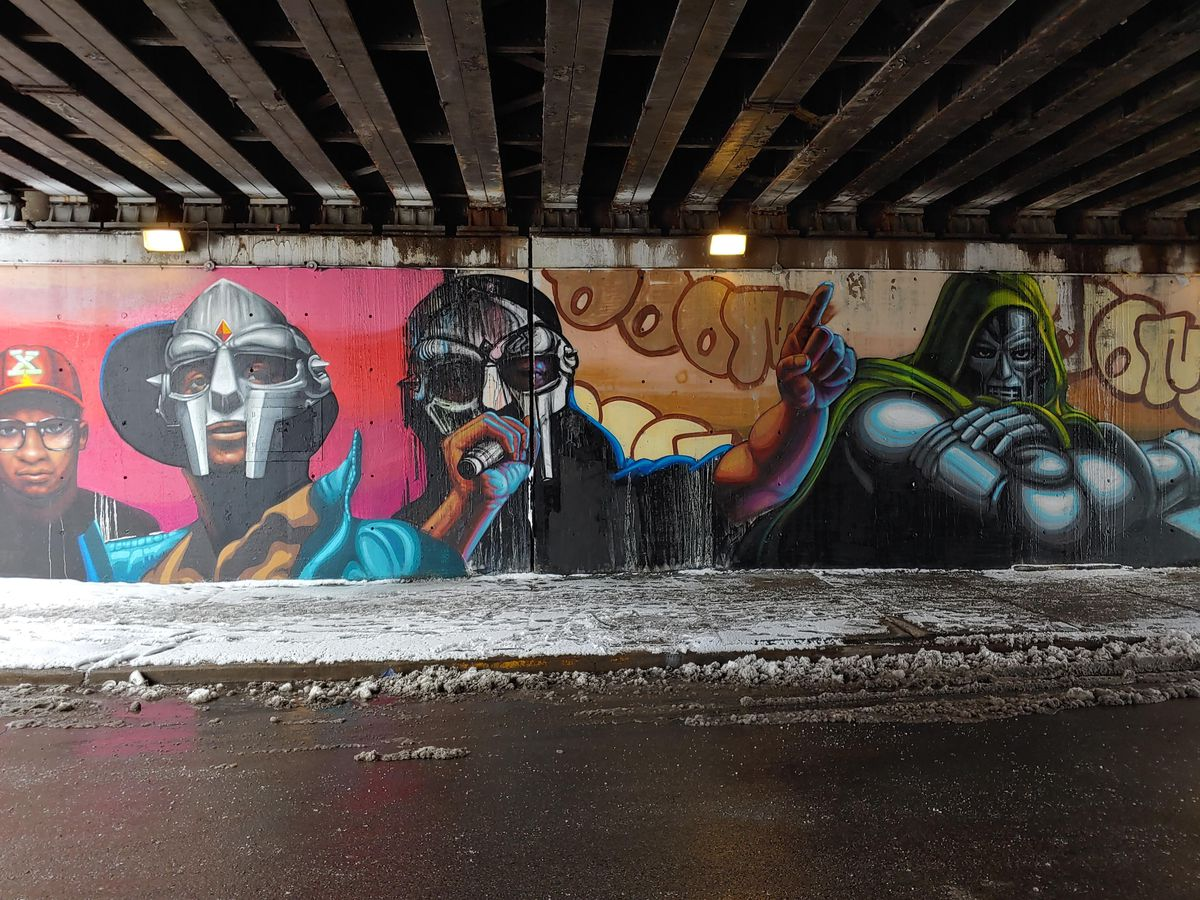 """The word """"DOOM"""" floats across the background of the right side of this mural by Chicago artist Rahmaan Statik."""