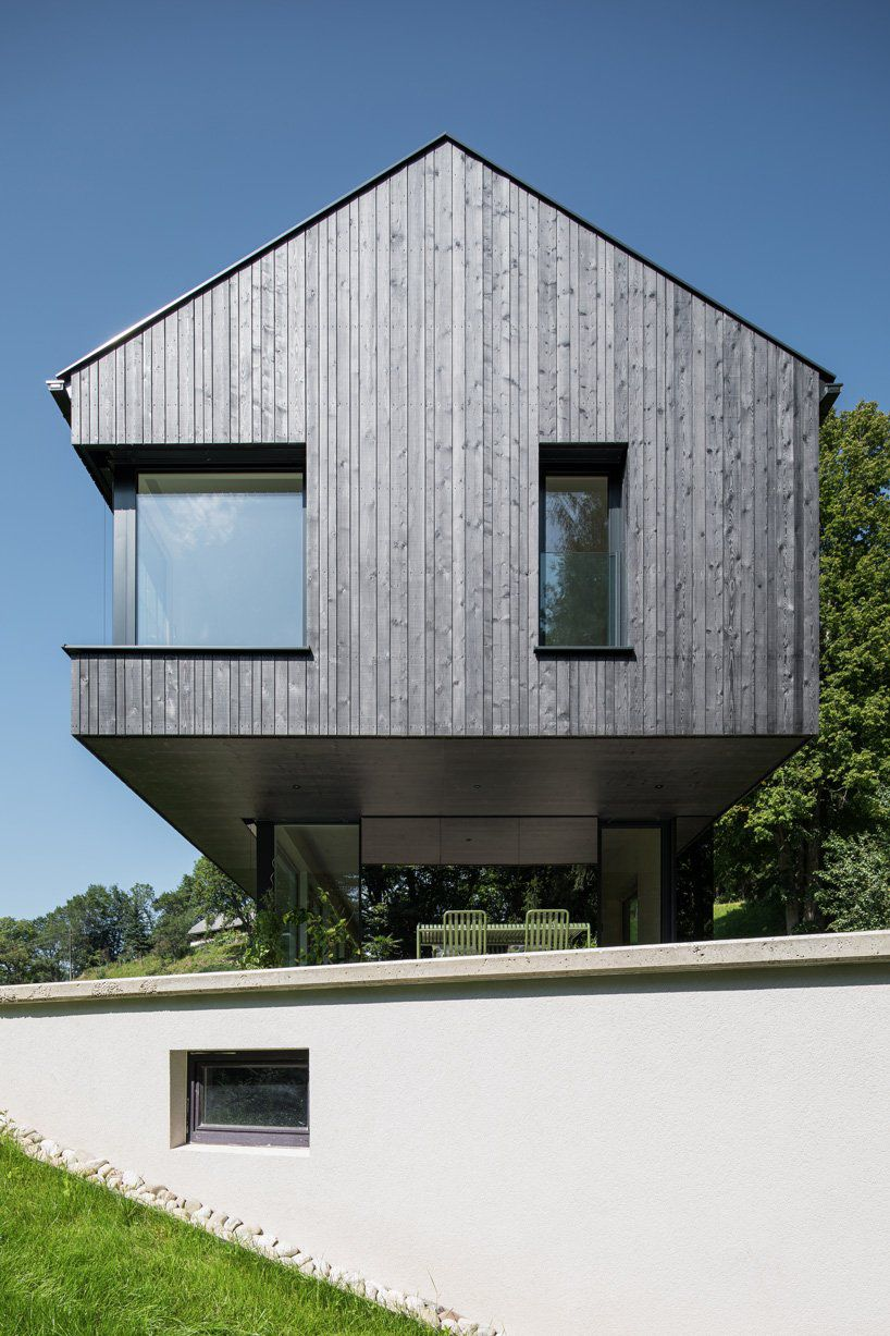 A pitch-roofed house with charred wood walls, and square and rectangle windows. The upper level juts out to shade an outdoor space underneath.