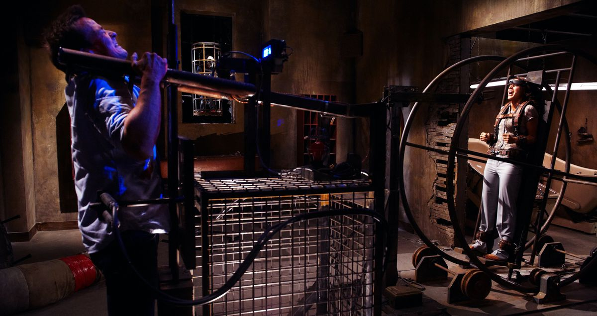 A man heaves on an elaborate machine as a woman screams from a different part of the machine in Saw 3D