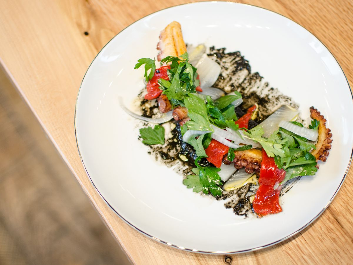 Overhead shot of a charred octopus tentacle on a white plate, garnished with a black sauce, pickled fennel, and bright red peppers. It's on a light wooden table; a wooden floor is visible underneath.