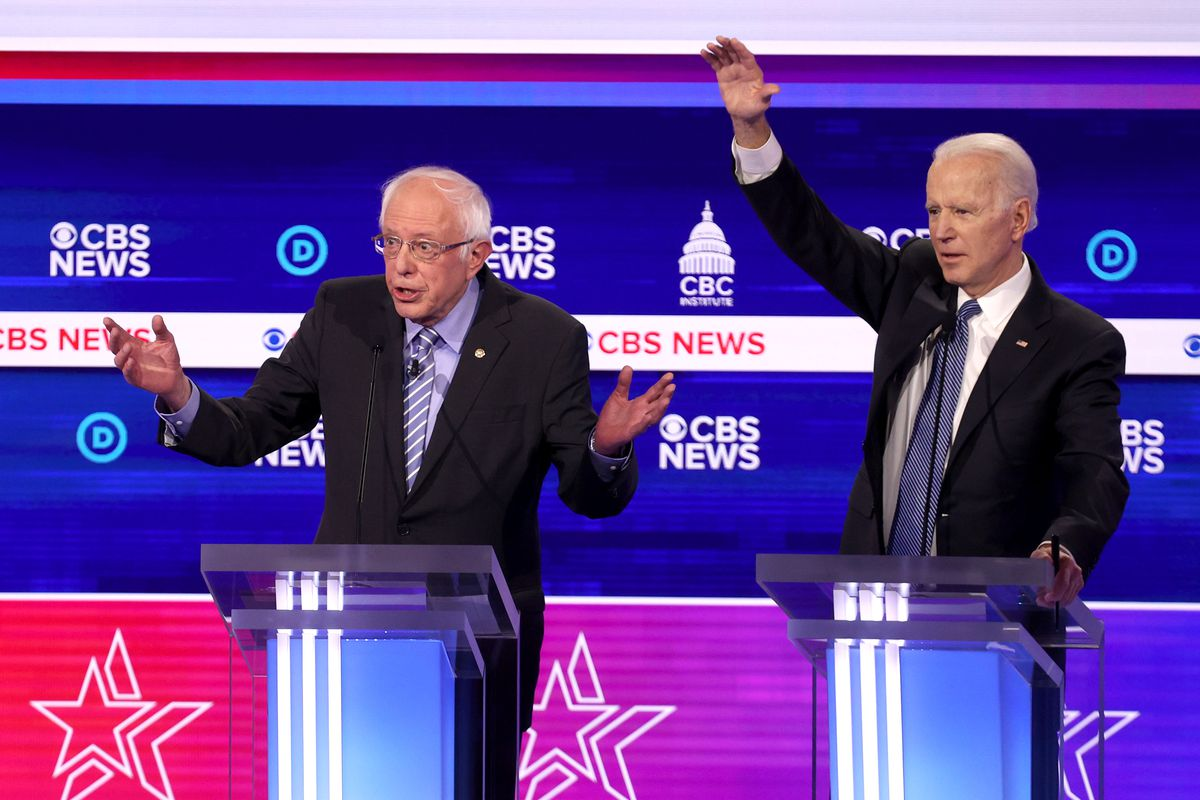 Senator Bernie Sanders and former Vice President Joe Biden stand onstage behind podiums with their arms raised.