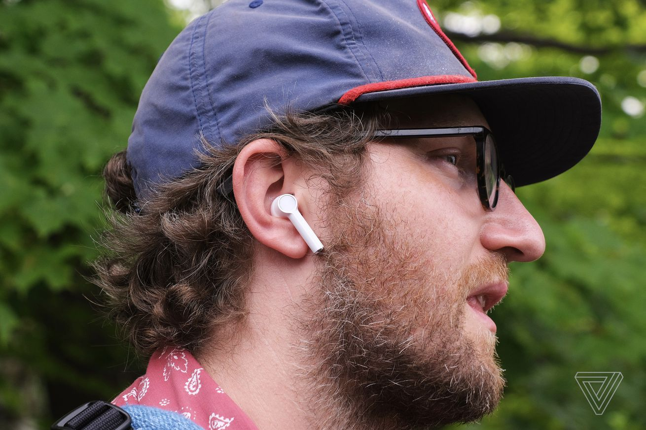 A person wearing the OnePlus Buds earbuds.