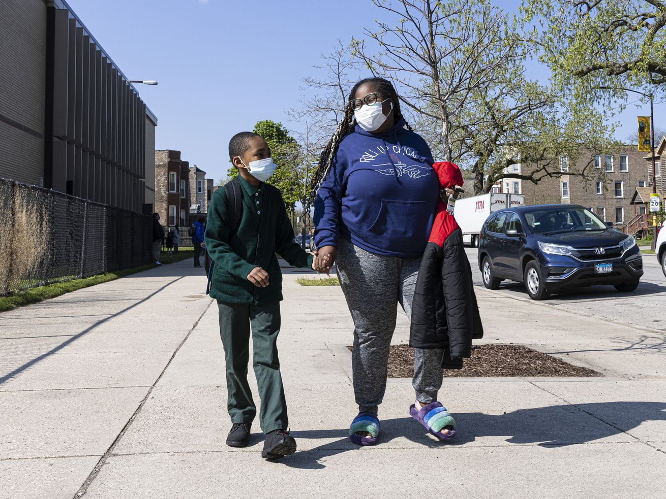 Alanna Barber and her son Sean Smith, 8, walk back to their vehicle after school outside of Beasley Elementary in Washington Park, Thursday, April 29, 2021.