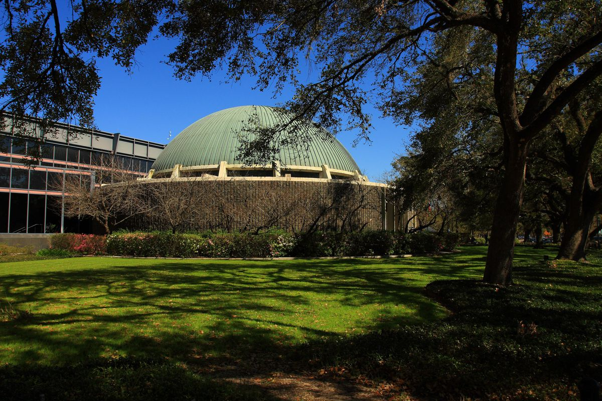The exterior of the Burke Baker Planetarium at the Houston Museum of Natural Science. The roof is painted green and dome shaped. There are trees and grass in front.