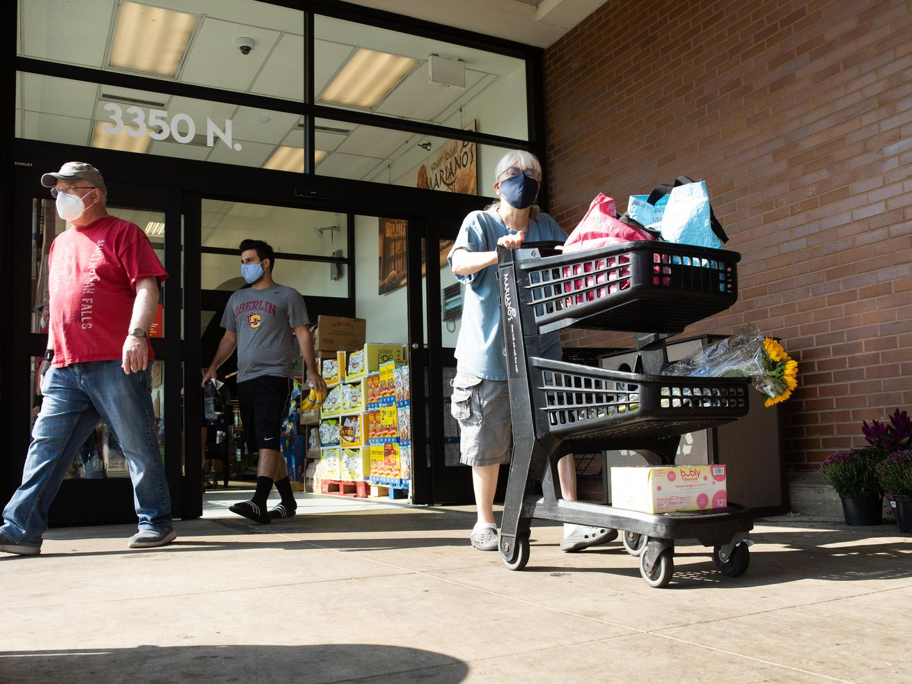 People exit Mariano's in the Roscoe Village neighborhood, Friday morning, Aug. 20, 2021. An indoor mask mandate for both vaccinated and unvaccinated people two years old or older took effect again on Friday to stop the spread of COVID-19 as cases rise due to the Delta variant.