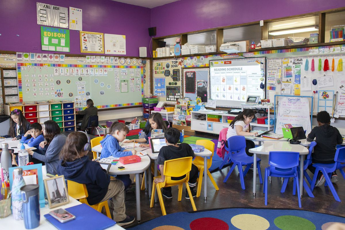 Students at CICS West Belden school work in the classroom. They sitting on brightly colored chairs around tables at the Chicago charter school. The walls are decorated with posters.