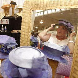 Diane Van Trees of Waikiki tries on a hat at this year's Made in Hawaii Festival. The festival started five years ago with 61 merchants and has expanded to 410.