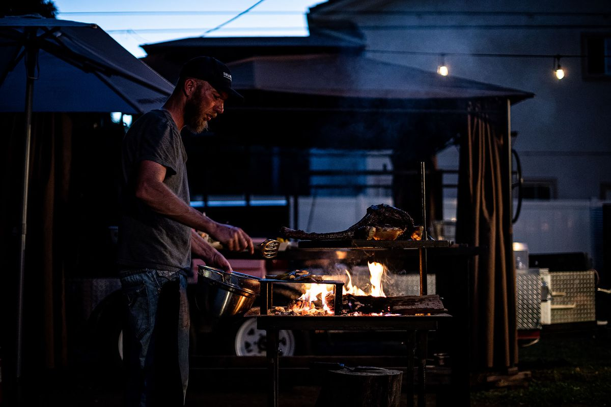 A chef turns a steak over a large flame as night falls.