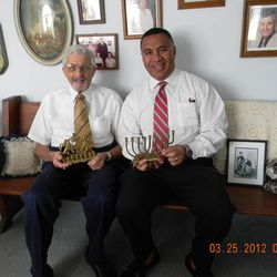 Marty and Vai holding Klein family heirlooms – Jewish menorahs.