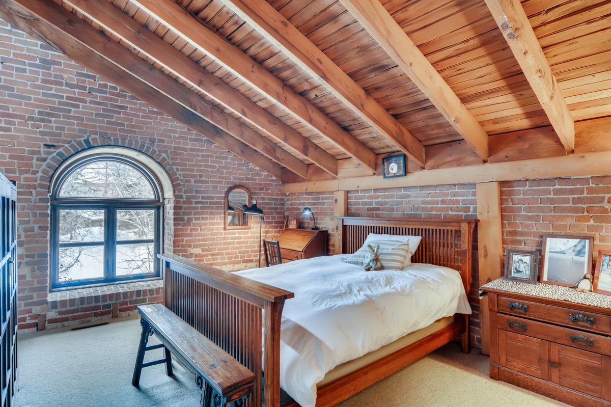 A white comforter on a wooden bed sits in a bedroom with brick walls.