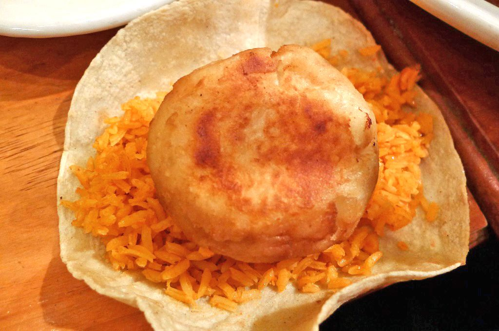 A tortilla with rice and a round fried potato patty.