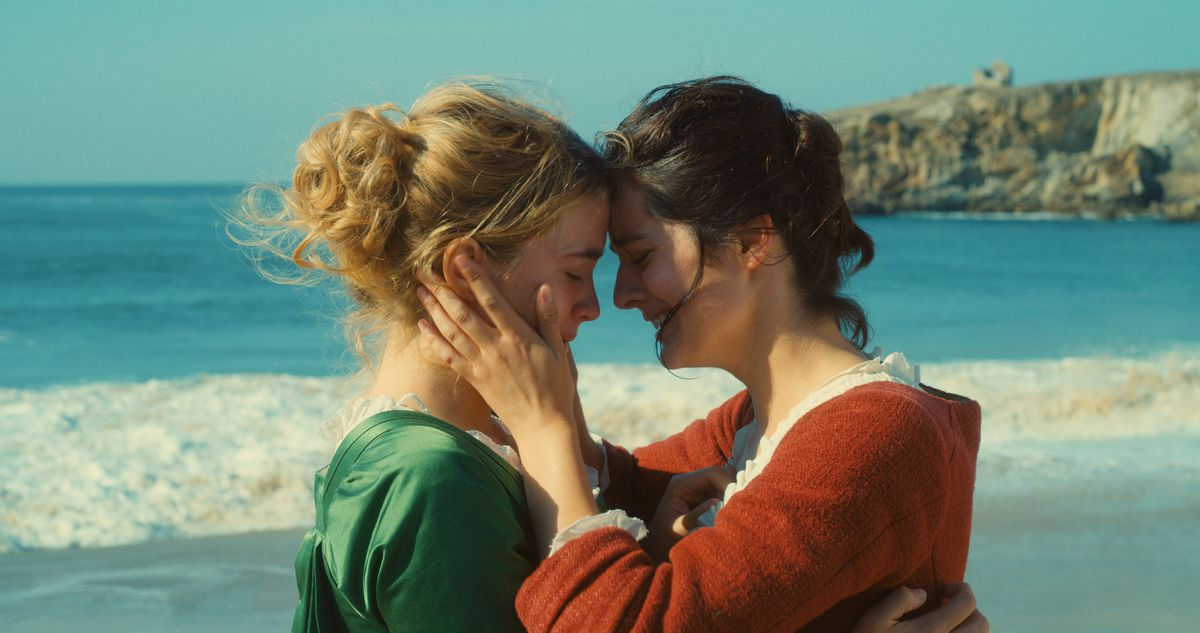 The two women hold each other close on the beach.