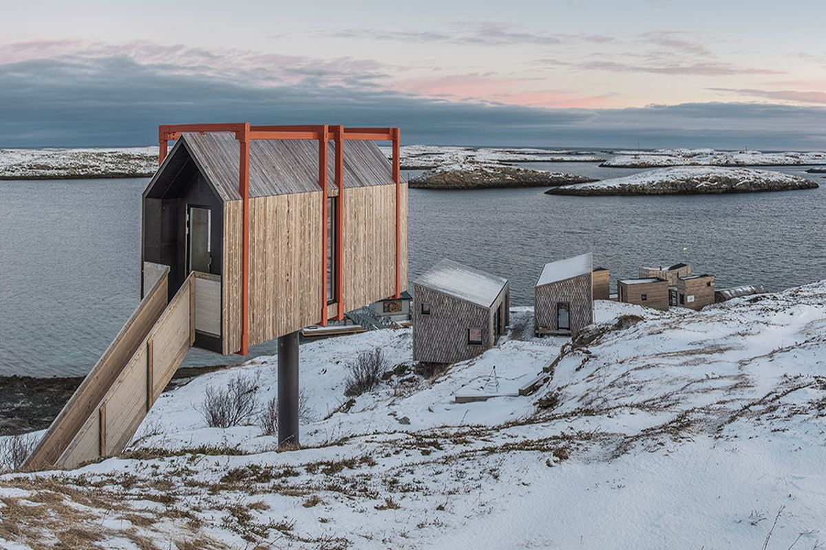 A cabin perched on a pillar on a rugged hillside coastal site, with a cluster of cabins below.