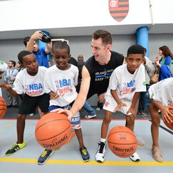 Magic center Jason Smith assists with a basketball clinic in Rio for local school children.