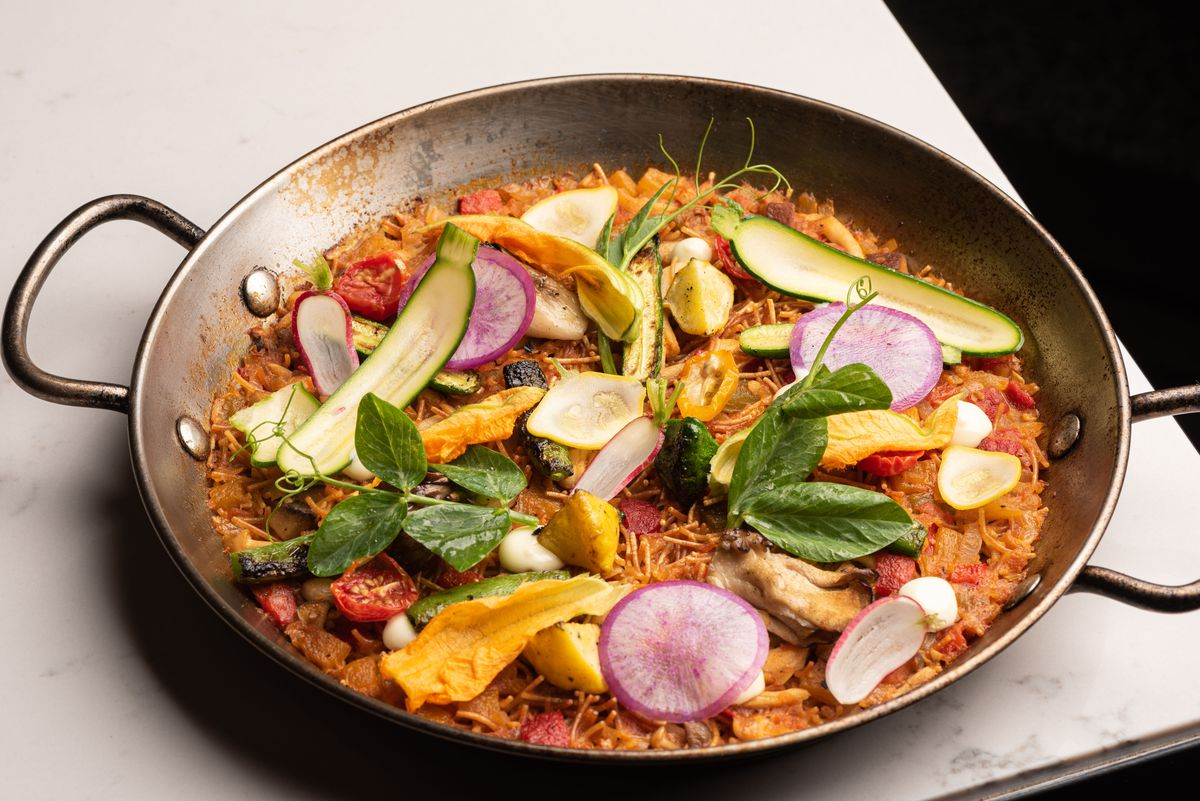 A paella pan with Spanish rice and topped with lots of colorful vegetables.