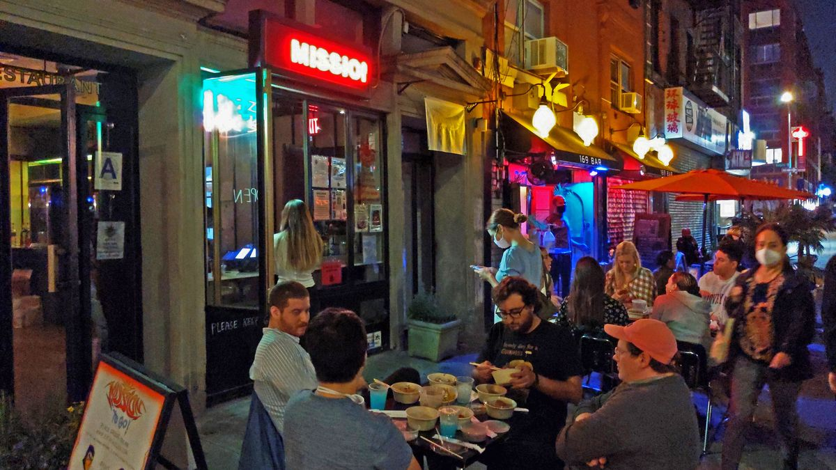 A sidewalk seating area by night, a table of diners in the foreground and a sign glowing Mission.