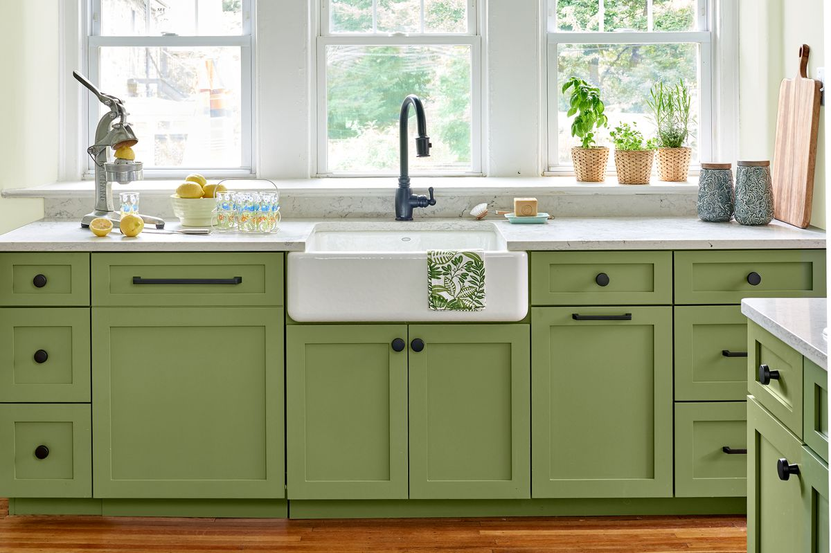 Kitchen with green cabinets and a farm sink.