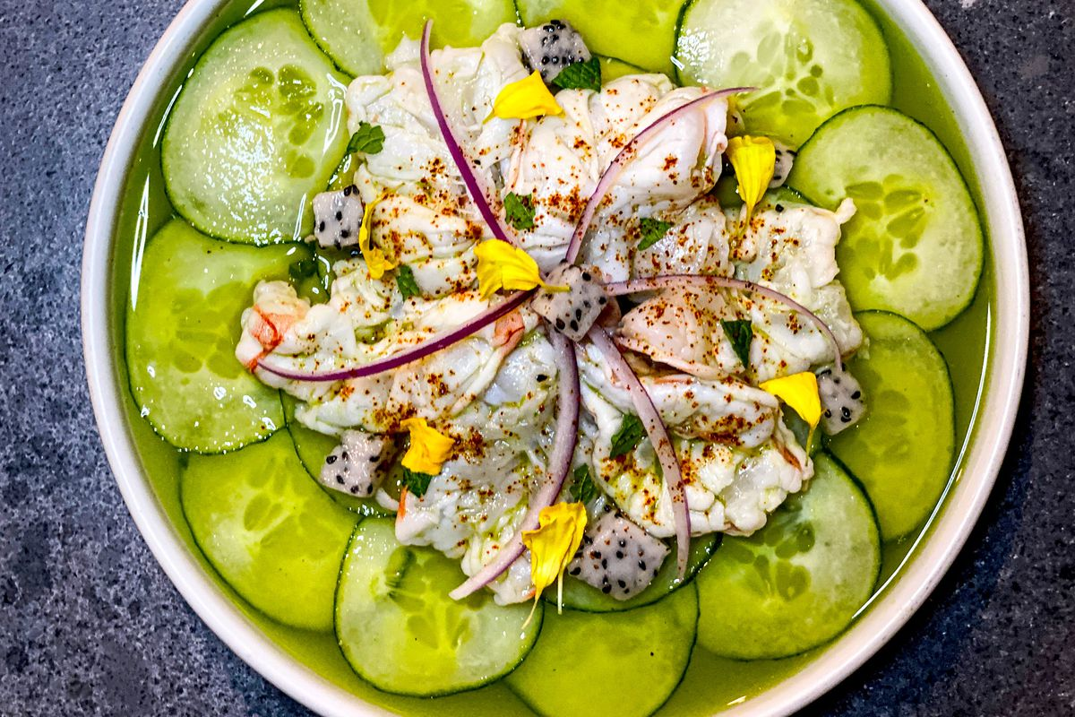 A pile of shrimp ceviche garnished with colorful flecks of vegetables sits atop a concentric circle of cucumber slices