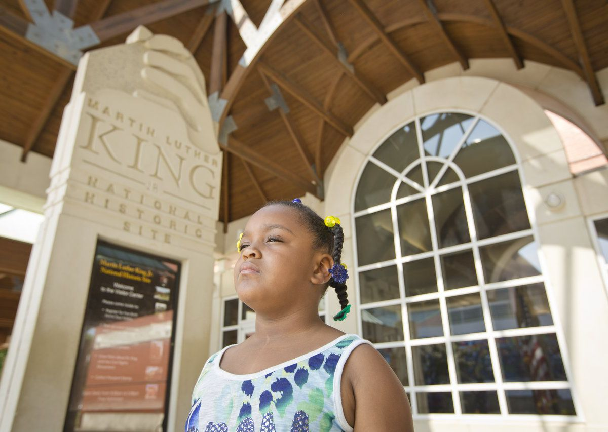 A young girl stands outside of a visitor's center building which has large windows. There is a wall with words on it which reads: Martin Luther King National Historic Site.