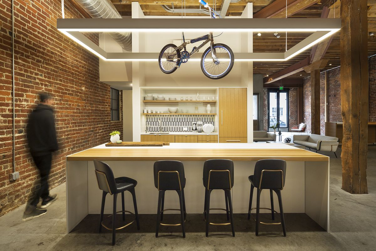 A kitchen has a eat-in bar. A kid's dirt bike hangs above it.