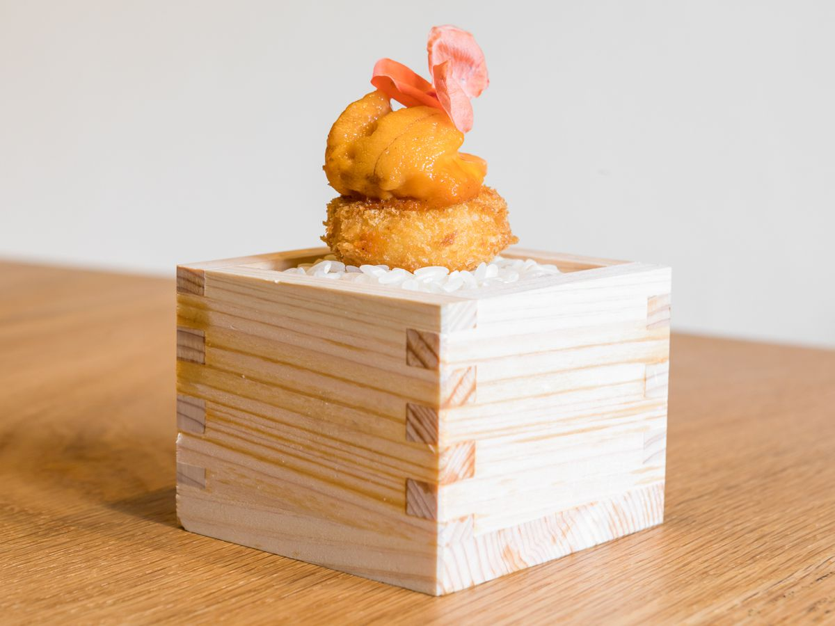 Japanese croquette topped with uni and a fermented carrot at restaurant Nisei