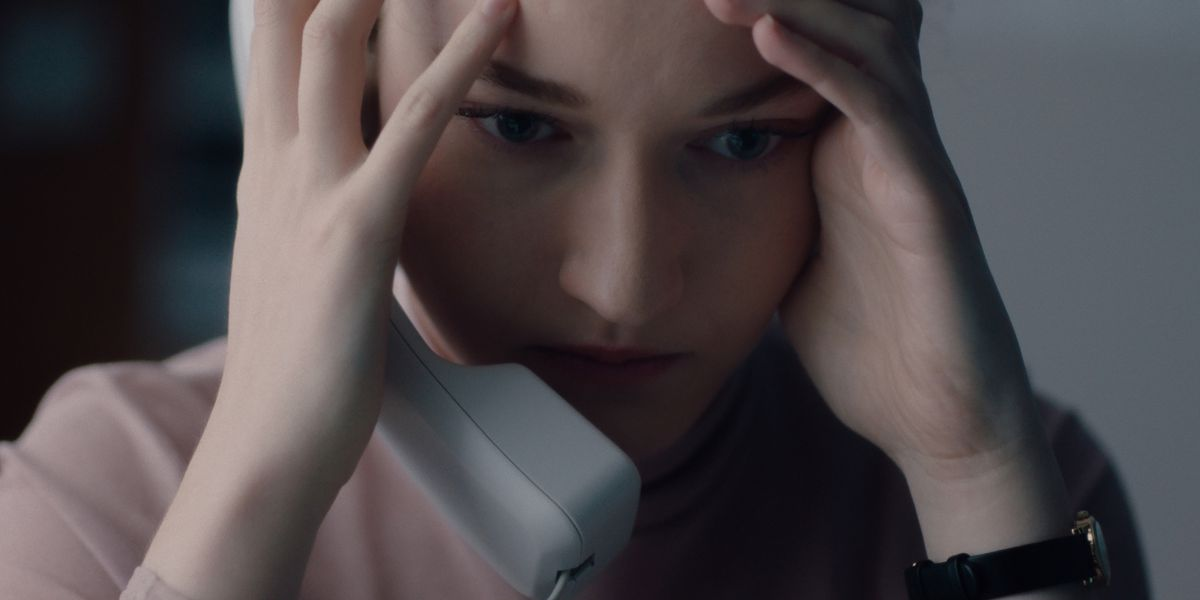 a woman on the phone holds her head in her hands
