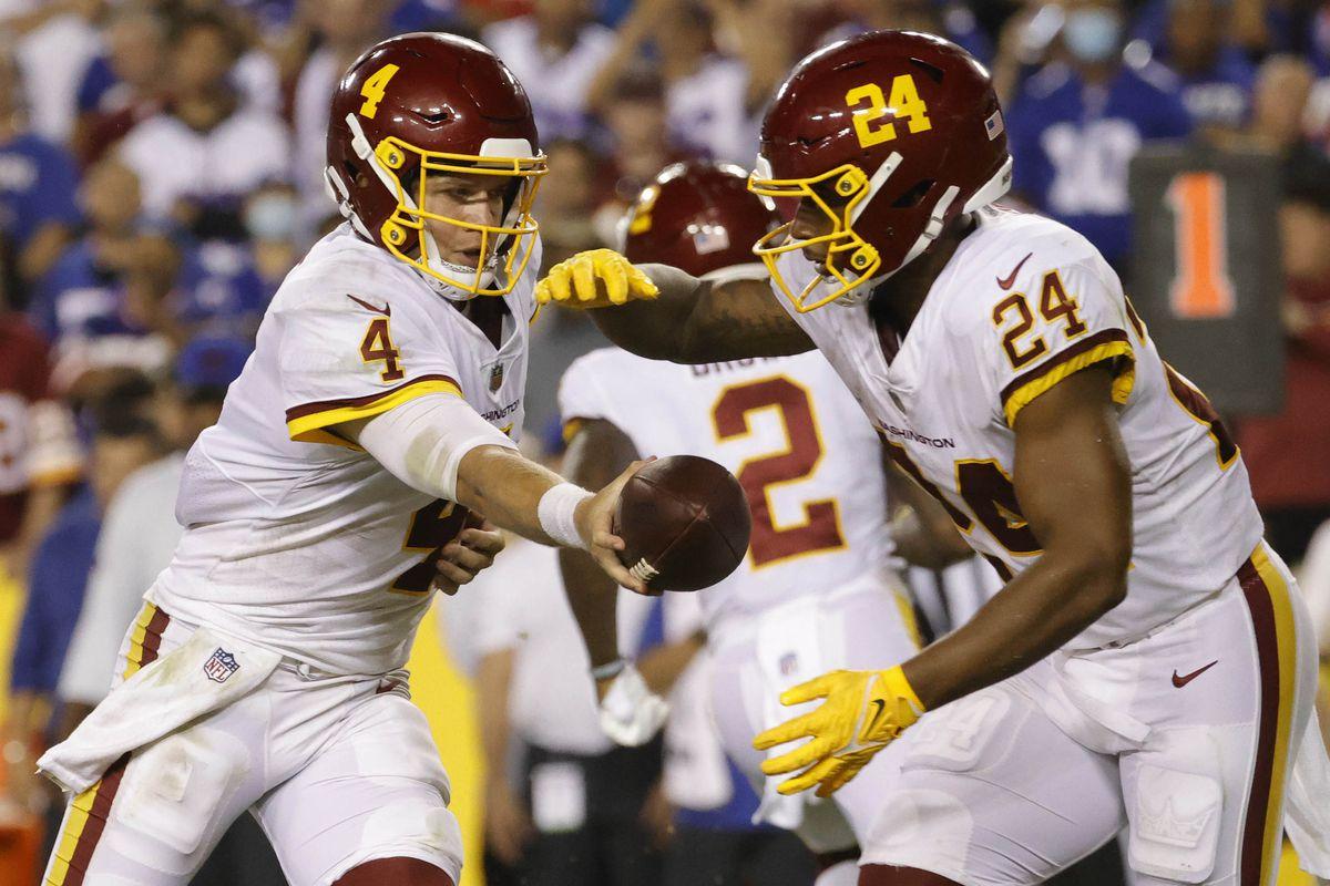 Washington Football Team quarterback Taylor Heinicke (4) hands the ball off to Washington Football Team running back Antonio Gibson (24) against the New York Giants at FedExField.