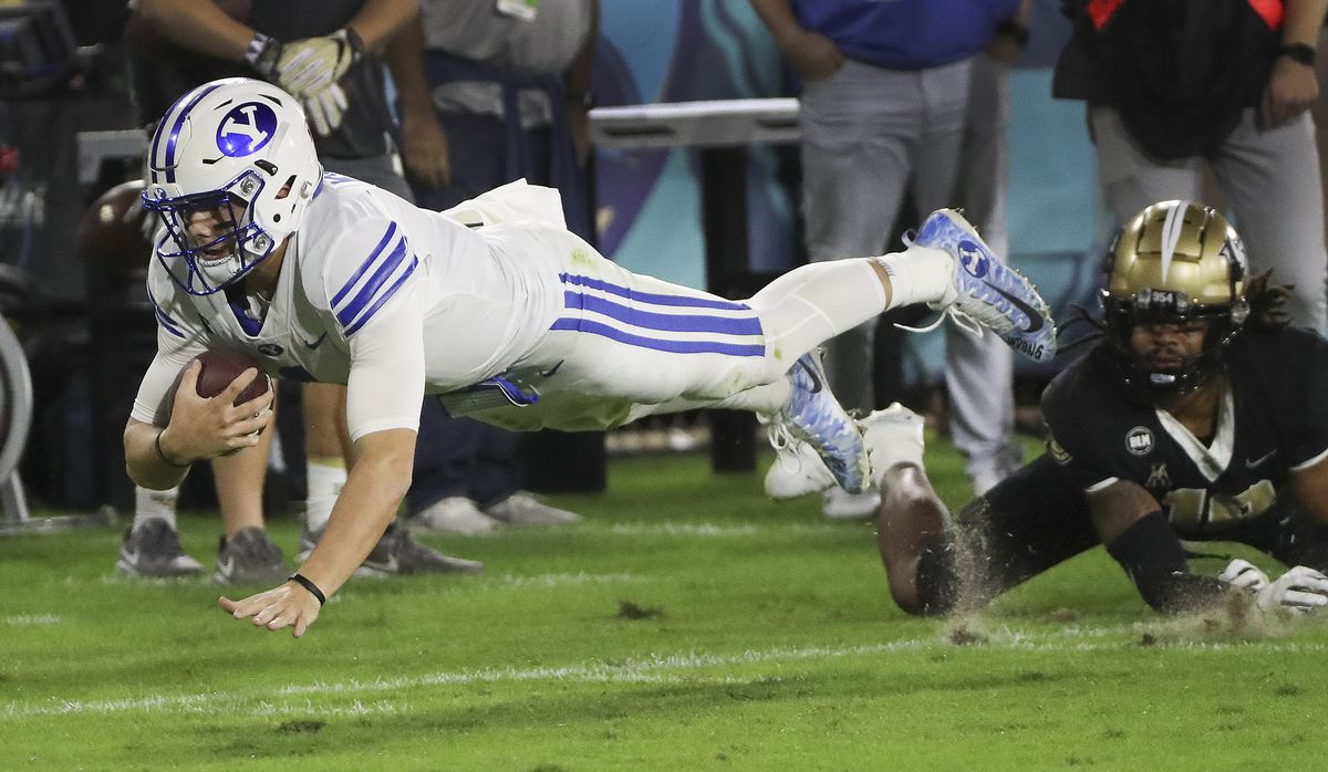 Brigham Young Cougars quarterback Zach Wilson dives for additional yards after catching a pass against the UCF Knights during the Boca Raton Bowl in Boca Raton, Fla., on Tuesday, Dec. 22, 2020.