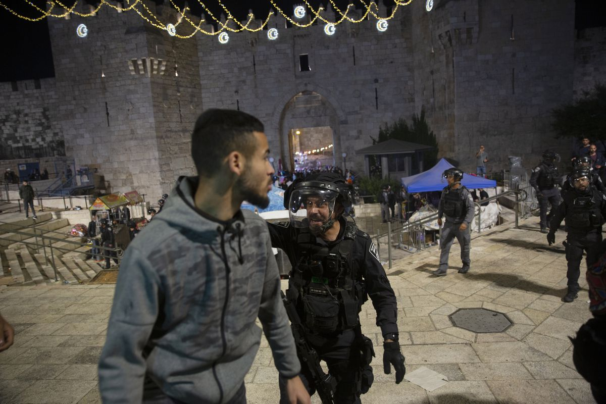 An Israeli policeman shouts at a Palestinian man to leave the Damascus Gate to the Old City of Jerusalem after clashes at the Al-Aqsa Mosque compound, Friday, May 7, 2021. Palestinian worshippers clashed with Israeli police late Friday at the holy site sacred to Muslims and Jews, in an escalation of weeks of violence in Jerusalem that has reverberated across the region.