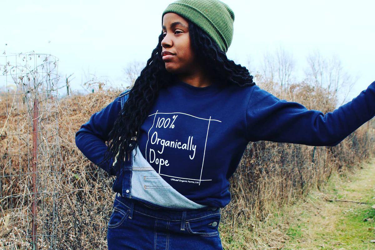 FarmerJawn's Christa Barfield wearing a 100% organically dope sweatshirt in a field in Elkins Park