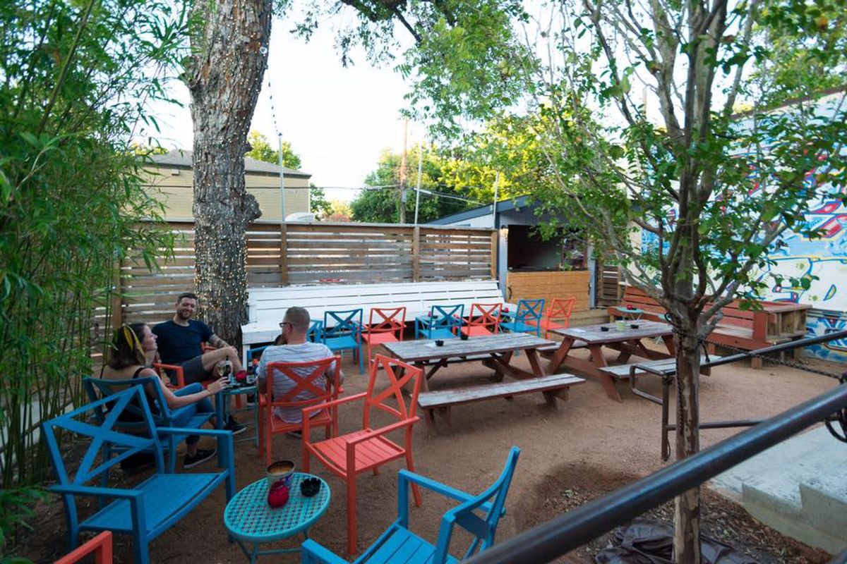 An outdoor seating area with colorful chairs, tables, and wooden picnic tables