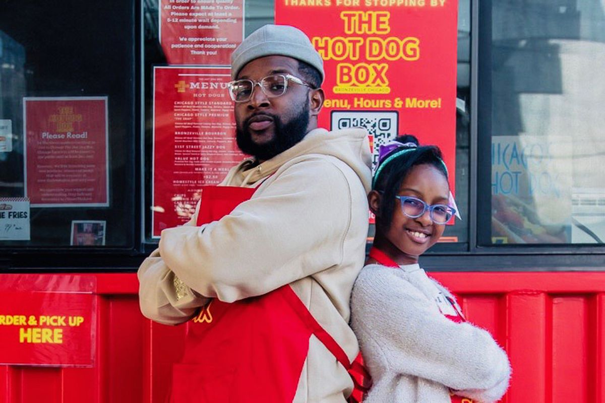 A man and his daughter wearing red aprons pose back-to-back in front of a red shipping container.