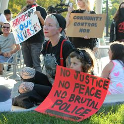 Rachel Harris and her 4-year-old daughter, Cleo, listen to speakers during a rally in Salt Lake City on Saturday, Sept. 2, 2017. Nearly 100 people gathered in Salt Lake City at a rally protesting police conduct against a University Hospital nurse who refused to allow a blood draw from an unconscious patient.
