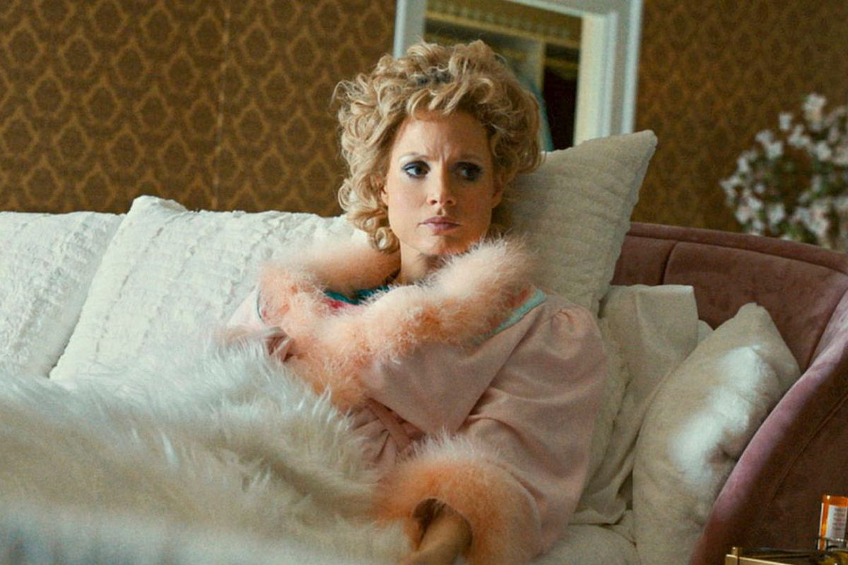 """Jessica Chastain, in silk bed robes and blonde hair, in bed in the film """"The Eyes of Tammy Faye."""""""