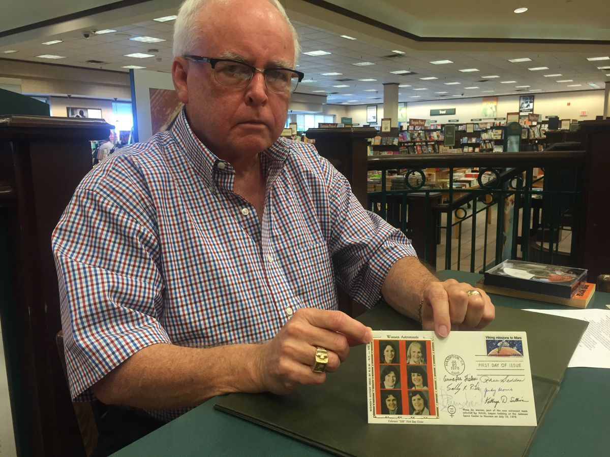 Retired planetarium director Duncan Teague poses with a U.S. postage stamp sleeve signed by the first six women in space.