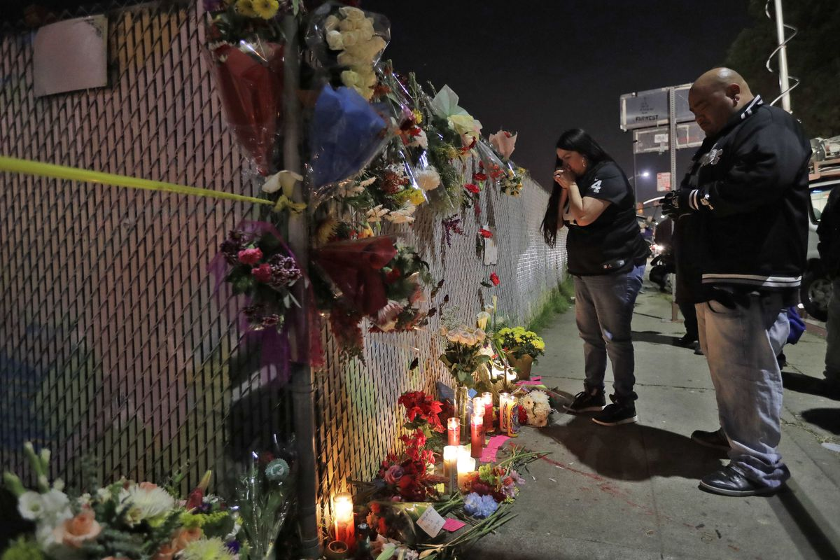 Sol Rodriguez, center, and Aaron Torres visit a shrine for the victims of the fire near the site.