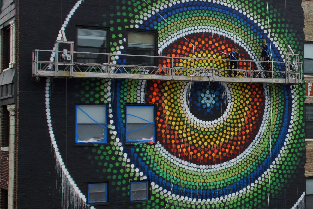 """Joe Miller and Sunni DiLuzio working from a swing stage on the mural """"Uptown Dot King."""""""
