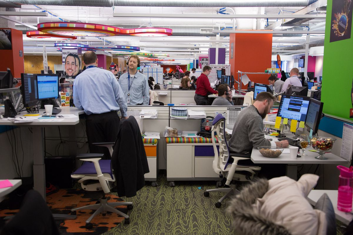 """Quicken Loans salespeople work at desks festooned with giant """"Fatheads"""" of each of their faces."""