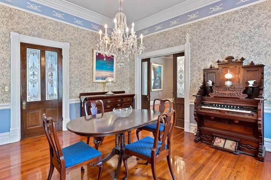 A dining room area with an ornate piano at right.