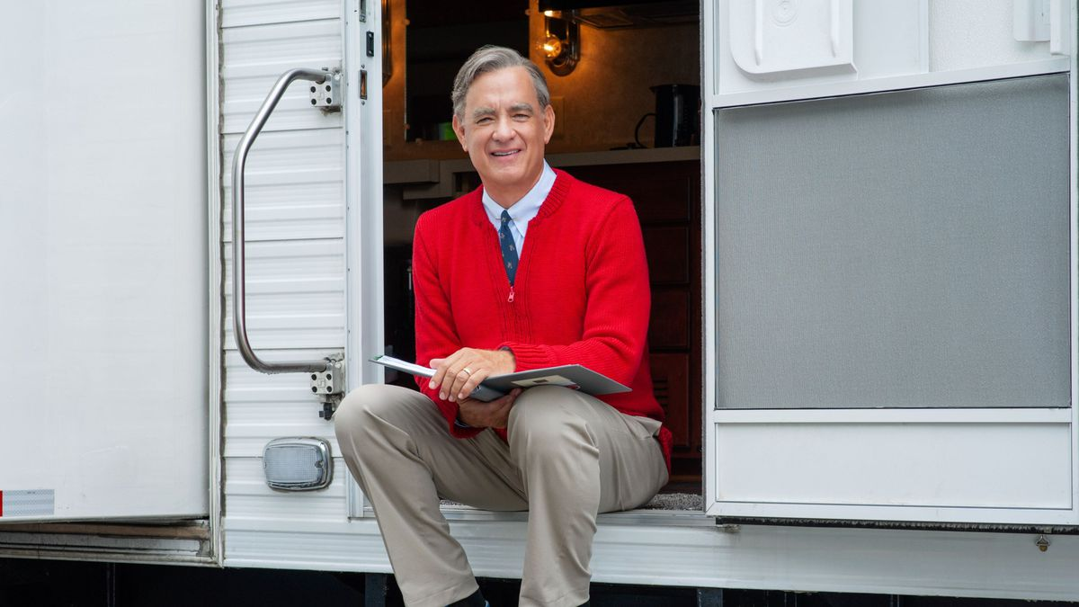 Tom Hanks as Fred Rogers in A Beautiful Day in the Neighborhood, sitting on the steps of his trailer wearing khakis and a red cardigan.