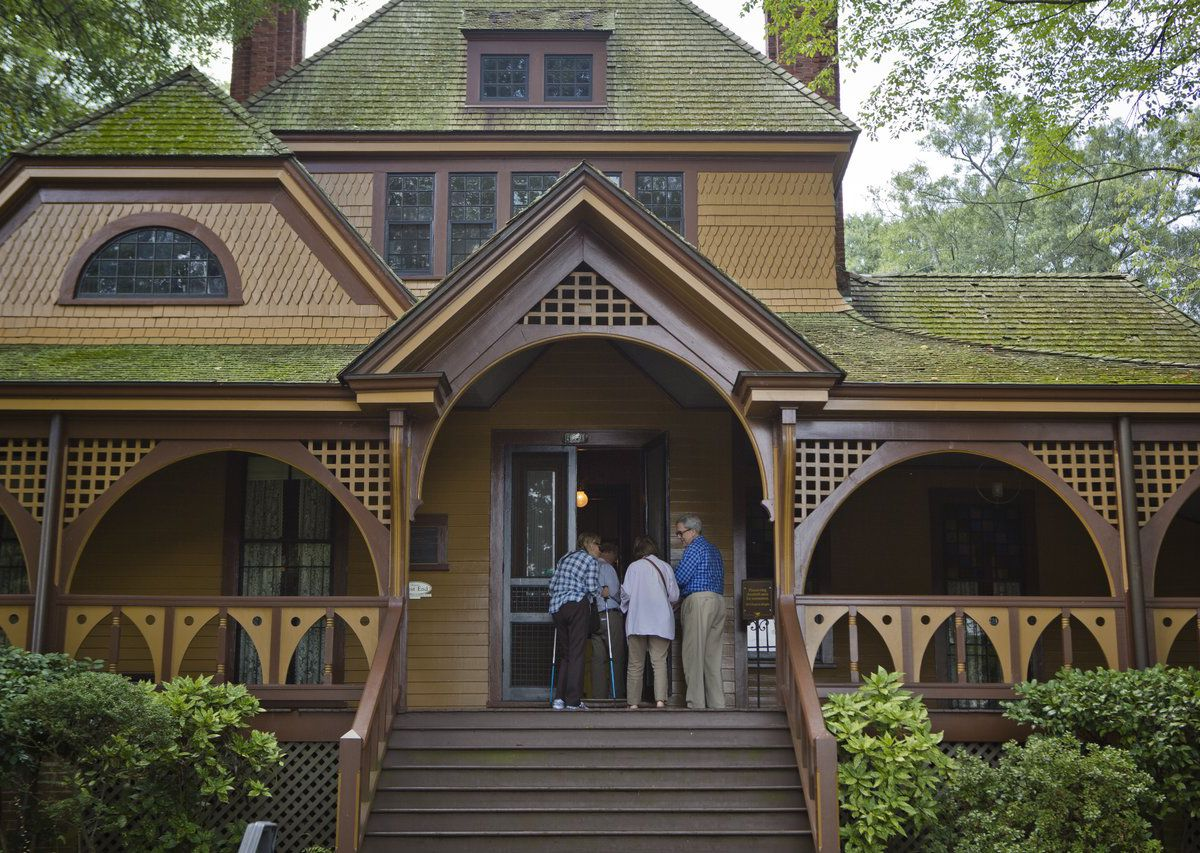 Three people entering the front door of a brown house with green roofing.